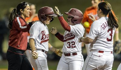 FILE - In this Feb. 21, 2014 file photo, Alabama associate head coach Alyson Habetz, left, Ryan Iamurri (32) and Peyton Grantham (3) greet Danielle Richard (19) as she returns from second after batting in the game-ending RBI during an NCAA college softball game against Virginia Tech, in Tuscaloosa, Ala. Alabama's Jaclyn Traina and Ryan Iamurri are trying to end their careers with a second title in three years at the Women's College World Series, which starts Thursday.  (AP Photo/AL.com, Vasha Hunt) MAGS OUT