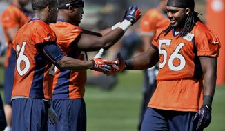 Denver Broncos linebacker Nate Irving (56) shakes hands with safety Rahim Moore (26)  before the start of an NFL football organized team activity, Wednesday, May 28, 2014, in Englewood, Colo. (AP Photo/Jack Dempsey)