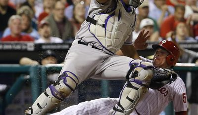Philadelphia Phillies' Carlos Ruiz, right, collides with Colorado Rockies catcher Wilin Rosario after being forced out at home on a ball hit by Ben Revere during the third inning of a baseball game, Tuesday, May 27, 2014, in Philadelphia. (AP Photo/Matt Slocum)