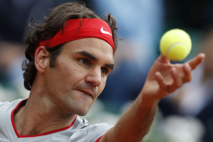 Switzerland's Roger Federer serves the ball during the second round match of the French Open tennis tournament against Argentina's Diego Sebastian Schwartzman at the Roland Garros stadium, in Paris, France, Wednesday, May 28, 2014. (AP Photo/Darko Vojinovic)