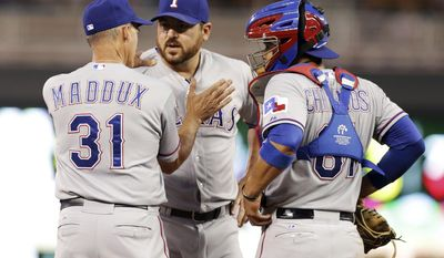 Texas Rangers pitching coach Mike Maddux, left, pats pitcher Joe Saunders, center, during a mound visit along with catcher Robinson Chirinos in the fifth inning of a baseball game against the Minnesota Twins, Wednesday, May 28, 2014, in Minneapolis. (AP Photo/Jim Mone)