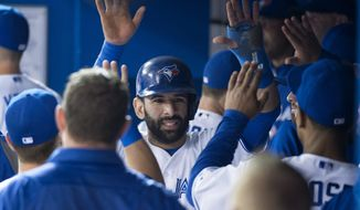 Toronto Blue Jays' Jose Bautista celebrates in the dugout after scoring on an Edwin Encarnacion two-run single against the Tampa Bay Rays in the first inning of a baseball game in Toronto on Wednesday, May 28, 2014. (AP Photo/The Canadian Press, Darren Calabrese)