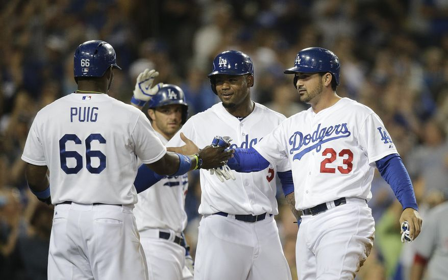 Los Angeles Dodgers' Yasiel Puig, Carl Crawford and Adrian Gonzalez, from left, celebrate after they scored on a triple hit Andre Ethier during the fourth inning of a baseball game against the Cincinnati Reds on Tuesday, May 27, 2014, in Los Angeles. (AP Photo/Jae C. Hong)