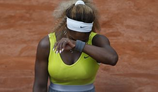 Serena Williams of the U.S. covers her face after missing a return during the second round match of the French Open tennis tournament against Spain's Garbine Muguruza at the Roland Garros stadium, in Paris, France, Wednesday, May 28, 2014. Williams lost in two sets 2-6, 2-6. (AP Photo/Darko Vojinovic)