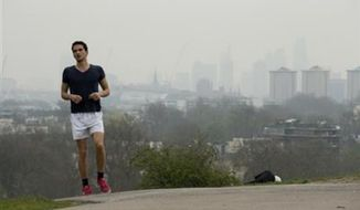 ** FILE ** A man jogs up Primrose Hill as buildings in central London stand shrouded in smog, Thursday, April 3, 2014. (Associated Press)