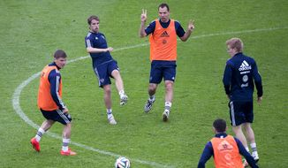 Russia's national soccer team players Sergei Ignashevich, center, Dmitri Kombarov, second from left, and Igor Denisov, left, attend a training session ahead of the 2014 World Cup in Brazil at the Eduard Streltsov Stadium in Moscow, Russia, Wednesday, May 28, 2014. Russia will play with South Korea, Algeria and Belgium in the Group H of World Cup soccer matches. (AP Photo/Pavel Golovkin)