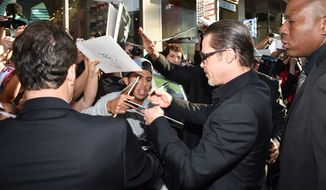 """Brad Pitt signs autographs at the world premiere of """"Maleficent"""" at the El Capitan Theatre on Wednesday, May 28, 2014, in Los Angeles. (Photo by John Shearer/Invision/AP)"""