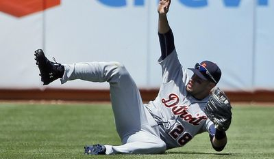 Detroit Tigers left fielder J.D. Martinez makes a sliding catch on a line drive from Oakland Athletics' Yoenis Cespedes during the fifth inning of a baseball game Thursday, May 29, 2014, in Oakland, Calif. (AP Photo/Marcio Jose Sanchez)