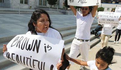 **FILE** Eva Cardenas, a community organizer who works for Georgia Latino Alliance for Human Rights, marches in front of the Federal Court with other protesters in Atlanta on June 20, 2011. (Associated Press)