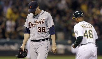 Detroit Tigers pitcher Joe Nathan (36) walks off the field past Oakland Athletics first base coach Tye Waller (46) after allowing a three-run home run to Josh Donaldson during the ninth inning of a baseball game in Oakland, Calif., Wednesday, May 28, 2014. The Athletics won 3-1. (AP Photo/Jeff Chiu)