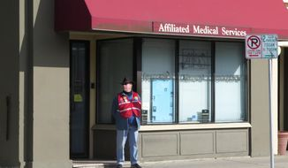 David Ritz, 65, stands as a volunteer escort outside Affiliated Medical Services, a Milwaukee abortion clinic, on Wednesday, May 28, 2014, in Milwaukee. From Texas to Alabama, laws are being enacted that would greatly restrict access to abortion, forcing many women to travel hundreds of miles to find a clinic. The laws, requiring abortion doctors to have privileges to admit patients to local hospitals, could have a profound impact on women in poor and rural sections of the Bible Belt. (AP Photo/Dinesh Ramde)