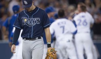 Tampa Bay Rays' Evan Longoria walks off the field as members of the Toronto Blue Jays celebrate their walk-off win over the Rays in a baseball game in Toronto on Wednesday, May 28, 2014. The Blue Jays defeated the Rays 3-2 and have extended their winning streak to nine games. (AP Photo/The Canadian Press, Darren Calabrese)