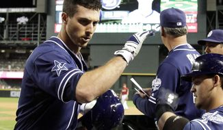 San Diego Padres first baseman Tommy Medica, left, celebrates with teammates after hitting a solo home run in the eighth inning during a baseball game against the Arizona Diamondbacks, Wednesday, May 28, 2014, in Phoenix. (AP Photo/Rick Scuteri)