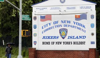 ** FILE ** In this May 17, 2011, file photo, a man walks near the sign at the entrance to the Rikers Island jail in New York. A Rikers Island jail guard who investigators say left her post without permission as a mentally ill inmate lay dying in his 101-degree cell in February had been disciplined four years earlier for a similar infraction, according to documents obtained by The Associated Press. (AP Photo/Seth Wenig, File)