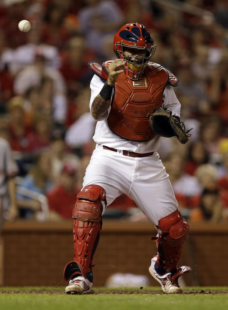 A ball thrown by St. Louis Cardinals center fielder Peter Bourjos gets past Cardinals catcher Yadier Molina allowing San Francisco Giants' Gregor Blanco to score during the eighth inning of a baseball game, Thursday, May 29, 2014, in St. Louis. Bourjos was charged with a throwing error on the play. (AP Photo/Jeff Roberson)