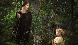 """Angelina Jolie as vengeful queen Maleficent looks down at her daughter Vivienne Jolie-Pitt, portraying Young Aurora, in a scene from """"Maleficent."""" (DISNEY VIA ASSOCIATED PRESS)"""