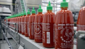 FILE - In the Tuesday, Oct. 29, 2013, file photo, Sriracha chili sauce is produced at the Huy Fong Foods factory in Irwindale, Calif. The Irwindale City Council voted Wednesday May 28, 2014 night to drop a public nuisance declaration and lawsuit against Huy Fong Foods, makers of Sriracha hot sauce. (AP Photo/Nick Ut, File)