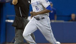 Kansas City Royals' Lorenzo Cain trots home from third as teammate Nori Aoki lies on the ground after being hit by pitch during sixth inning of a baseball game against the Blue Jays in Toronto, Thursday, May 29, 2014. The play was reviewed and home plate umpire Angel Hernandez sent Cain back to third. (AP Photo/The Canadian Press, Fred Thornhill)