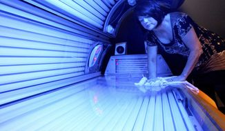 In this April 2, 2014 file photo, Teresa Lynch, owner of Dynamic Tanning in DeKalb, Ill., wipes down a tanning bed. (AP Photo/Daily Chronicle, Monica Maschak, File)  MANDATORY CREDIT **FILE**