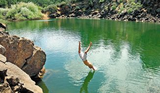 """In this photo taken on Wednesday, May 28, 2014, Tyson Scott, 20, of Medford dives into the """"Cove"""" swimming area at Emigrant Lake south of Medford, Ore. The lake is a favorite place for locals to cool off during the hot summer months. (AP Photo/The Medford Mail Tribune, Jamie Lusch)"""