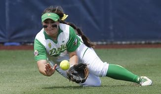 Oregon center fielder Koral Costa dives for and catches a ball hit by Florida State's Tiffani Brown for the out in the third inning of an NCAA Women's College World Series softball tournament game in Oklahoma City, Thursday, May 29, 2014. (AP Photo/Sue Ogrocki)