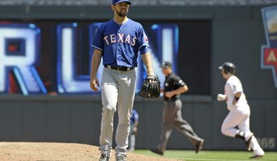 Texas Rangers pitcher Nick Martinez gives up a two-run home run to Minnesota Twins' Josh Willingham, right, in the fifth inning of a baseball game Thursday, May 29, 2014, in Minneapolis. (AP Photo/Jim Mone)