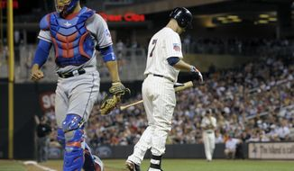 Minnesota Twins' Joe Mauer walks away after striking out in the seventh inning of a baseball game against the Texas Rangers, Wednesday, May 28, 2014, in Minneapolis. The Rangers won 1-0. At left is Rangers catcher Robinson Chirinos. (AP Photo/Jim Mone)