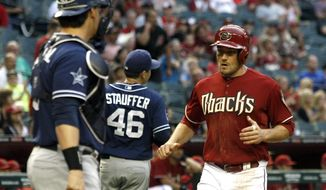 Arizona Diamondbacks center fielder A.J. Pollock, right, scores in the first inning during a baseball game against the San Diego Padres, Wednesday, May 28, 2014, in Phoenix. (AP Photo/Rick Scuteri)