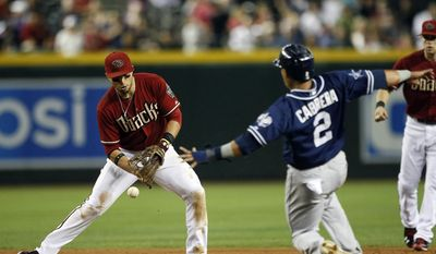 Arizona Diamondbacks third baseman Martin Prado, left, drops the ball trying to turn a double play in front of San Diego Padres shortstop Everth Cabrera (2) in the fifth inning during a baseball game, Wednesday, May 28, 2014, in Phoenix. (AP Photo/Rick Scuteri)