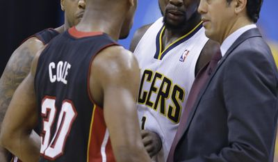 Indiana Pacers guard Lance Stephenson (1) joins a huddle as Miami Heat head coach Erik Spoelstra talks to Mario Chalmers, left and Norris Cole (30) during the second half of Game 5 of the NBA basketball Eastern Conference finals in Indianapolis, Wednesday, May 28, 2014. (AP Photo/Michael Conroy)