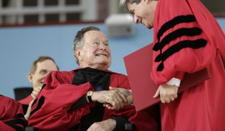 Former President George H. W. Bush, left, shakes hands with Vice President and Secretary of Harvard University Marc Goodheart, right, as Bush is awarded with an honorary Doctor of Laws degree during Harvard commencement ceremonies, Thursday, May 29, 2014, in Cambridge, Mass. (AP Photo/Steven Senne)