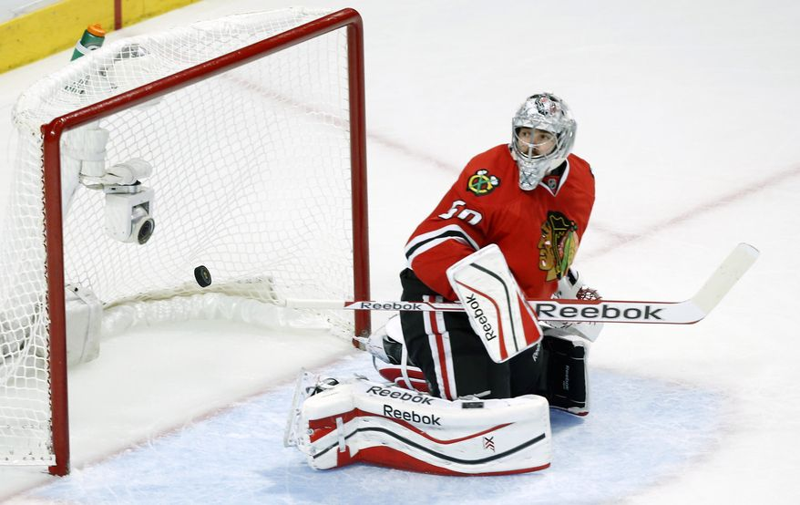 Chicago Blackhawks goalie Corey Crawford looks at the puck as Los Angeles Kings left wing Tanner Pearson shoots a goal during the second period in Game 5 of the Western Conference finals in the NHL hockey Stanley Cup playoffs Wednesday, May 28, 2014, in Chicago. (AP Photo/Andrew A. Nelles)
