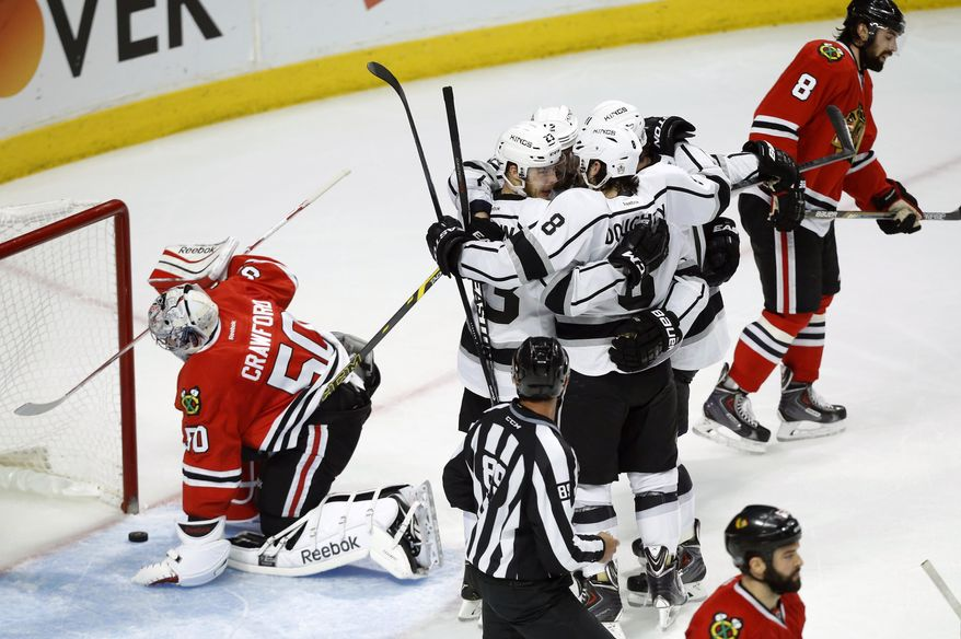 Los Angeles Kings right wing Dustin Brown (23) celebrates with his teammates after scoring a goal against Chicago Blackhawks goalie Corey Crawford (50) during the second period in Game 5 of the Western Conference finals in the NHL hockey Stanley Cup playoffs Wednesday, May 28, 2014, in Chicago. (AP Photo/Andrew A. Nelles)