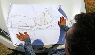 """FOR RELEASE SUNDAY, JUNE 1, 2014, AT 12:01 A.M. EDT - In this photo taken May 20, 2014, Mark Arena reviews a master plan design for pecan tree orchard at the entrance of Clemson University on S.C. 93 in Clemson, S.C.  It is part of the school's green footprint. """"Now it's going to come to fruition,"""" said Arena. (AP Photo/Independent Mail, Ken Ruinard) GREENVILLE OUT, SENECA OUT."""
