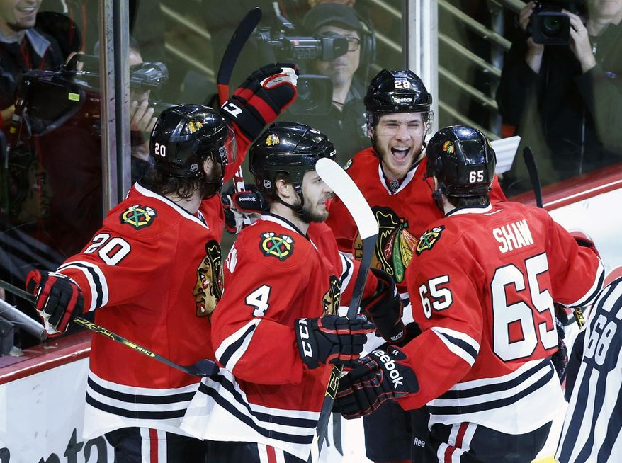 Chicago Blackhawks right wing Ben Smith, second from right, celebrates with his teammates after scoring a goal against Los Angeles Kings during the third period in Game 5 of the Western Conference finals in the NHL hockey Stanley Cup playoffs Wednesday, May 28, 2014, in Chicago. (AP Photo/Andrew A. Nelles)