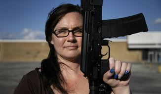 Tara Cowan of Euless, Texas, a member of Open Carry Tarrant County, poses for a portrait with a Saiga 556 rifle as she and members of the group Open Carry Tarrant County gathered for a demonstration, Thursday, May 29, 2014, in Haltom City, Texas. North Texas gun rights advocates are suing the city of Arlington for amending an ordinance that they claim is discriminatory and infringes upon free speech rights, in the latest sign of growing tensions among gun activists and government forces in Texas. (AP Photo/Tony Gutierrez)