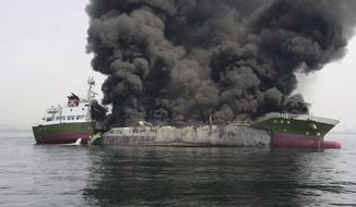 In this photo released by Japan's 5th Regional Coast Guard, clouds of black smoke billow from Shoko Maru, a 998-ton Japanese oil tanker, after it exploded off the southwest coast near Himeji port, western Japan, Thursday, May 29, 2014. One of the eight people aboard is missing and the other seven were injured, according to the coast guard. (AP Photo/Japan's 5th Regional Coast Guard)
