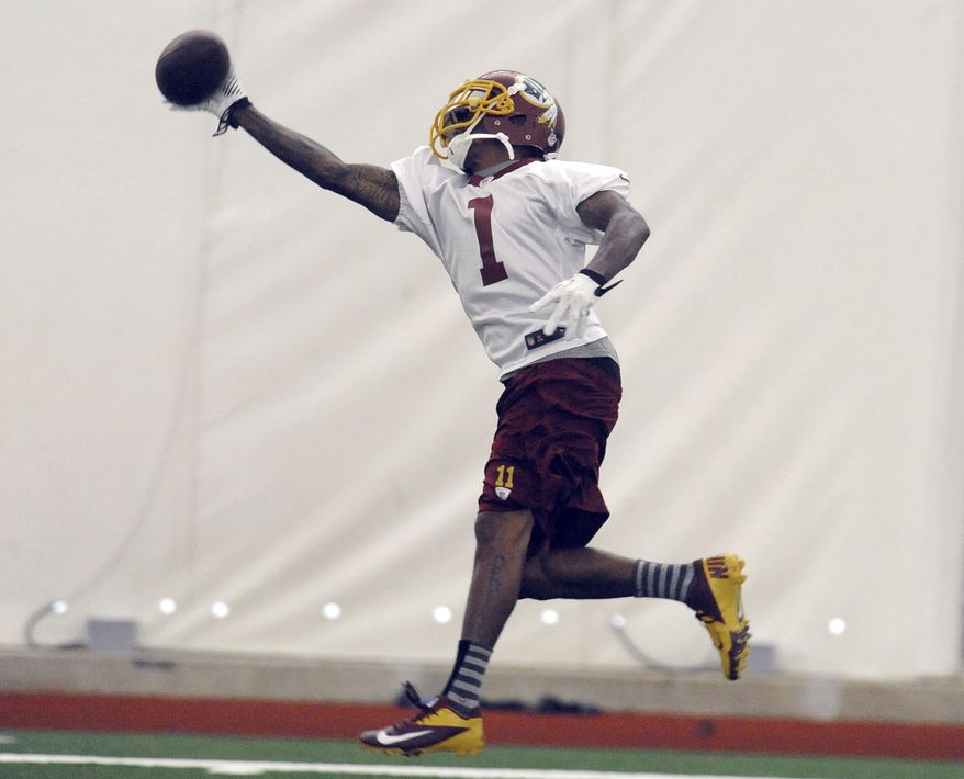 Washington Redskins wide receiver DeSean Jackson, reaches for a pass from Robert Griffin III  during their NFL organized team activity at Redskins training facility, Thursday, May 29, 2014, in Ashburn, Va. (AP Photo/Richard Lipski)