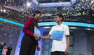 Ansun Sujoe, 13, of Fort Worth, Texas, left, and Sriram Hathwar, 14, of Painted Post, N.Y., shake hands after being named co-champions of the National Spelling Bee, on Thursday, May 29, 2014, in Oxon Hill, Md. (AP Photo/ Evan Vucci)