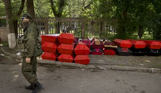 A pro-Russian gunman walks by coffins of those killed in fighting with Ukrainian troops for control of the city's airport at a morgue in Donetsk, Ukraine, Thursday, May 29, 2014. (AP Photo/Vadim Ghirda)