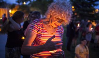 In this May 29, 2014 photo, Denee Mallon, center, participates in a candlelight vigil organized by Albuquerque Pride in Albuquerque, N.M. A U.S. Department of Health and Services review board ruled Friday, May 30, in favor of Mallon, a 74-year-old Army veteran, whose request to have Medicare pay for her genital reconstruction was denied two years ago. The decision recognizes sex reassignment surgeries as a medically necessary and effective treatment for individuals who do not identify with their biological sex. (AP Photo/Craig Fritz)