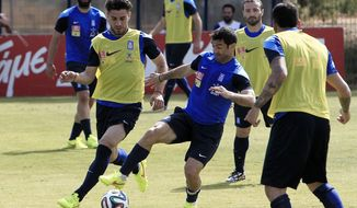 Greece's captains Giorgos Karagounis, right, and Kostas Katsouranis fight for the ball during a training session in Athens on Thursday, May 29, 2014. Greece trained for the last time in Athens before its departure on Friday abroad for preparations ahead the World Cup. The Greeks face Portugal Saturday in the first of three warm-up matches, and will arrive at the sports camp in Aracaju, Brazil on Saturday, June 7. Greece will play in Group C, against Colombia, Japan and Ivory Coast at the World Cup in Brazil. (AP Photo/Thanassis Stavrakis)