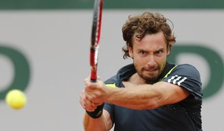 Latvia's Ernests Gulbis returns the ball during the third round match of the French Open tennis tournament against Radek Stepanek of the Czech Republic at the Roland Garros stadium, in Paris, France, Friday, May 30, 2014.  (AP Photo/David Vincent)