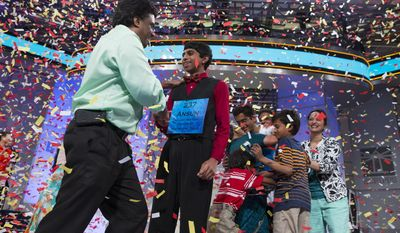 Ansun Sujoe, 13, of Fort Worth, Texas, left, and Sriram Hathwar, 14, of Painted Post, N.Y., celebrate with their families after being named co-champions of the National Spelling Bee, on Thursday, May 29, 2014, in Oxon Hill, Md. (AP Photo/ Evan Vucci)
