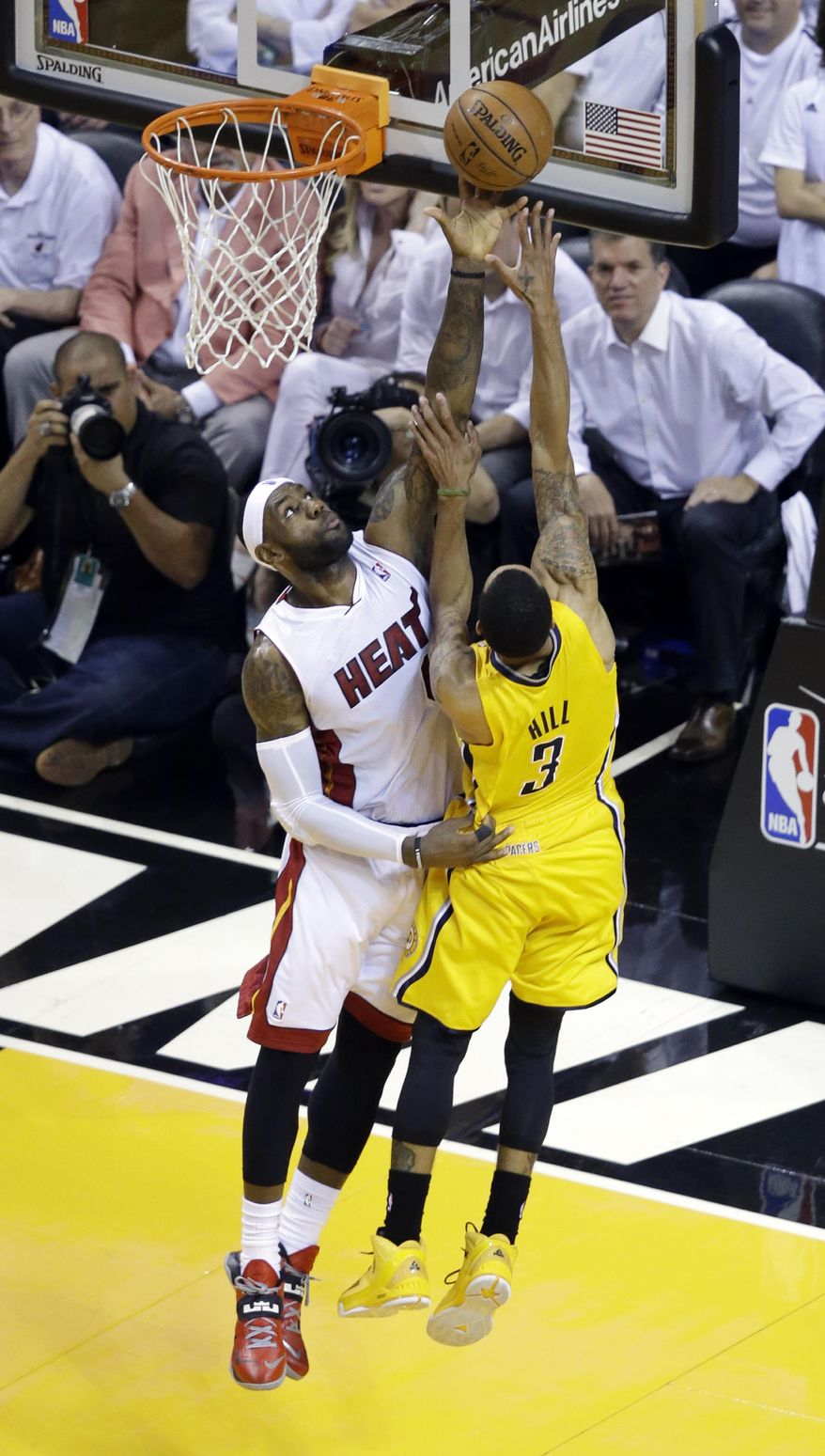 Miami Heat forward LeBron James, left, blocks a shot to the basket by Indiana Pacers guard George Hill (3), during the first half of Game 6 in the NBA basketball playoffs Eastern Conference finals on Friday, May 30, 2014 in Miami. (AP Photo/Wilfredo Lee)
