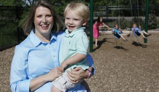 In this May 29, 2014 photo, Christy Wolford, a breast cancer survivor, holds her youngest son Lucas, 2, as her other children Lauren, 8, Alexander, 4, and Everett, 3, play on the swing in the background at her Primrose School in Fort Collins, Colo. Young women with breast cancer might be able to avoid infertility caused by chemotherapy if they use a drug to shut down their ovaries temporarily, while treatment goes on. Wolford's ovaries were suppressed during cancer treatment and she has had three boys since it ended in 2006. (AP Photo/Ed Andrieski)