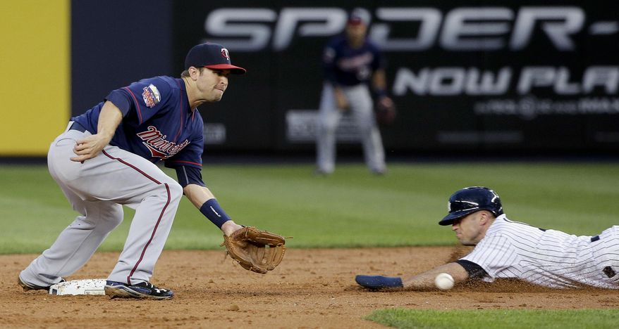 New York Yankees' Brett Gardner, right, slides safely into second base for a steal ahead of the throw to Minnesota Twins second baseman Brian Dozier, left, during the third inning of a baseball game on Friday, May 30, 2014, in New York. (AP Photo/Julie Jacobson)