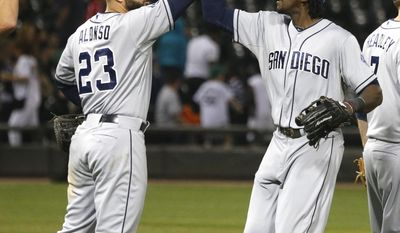 San Diego Padres first baseman Yonder Alonso (23) and center fielder Cameron Maybin celebrate the Padres' 4-1 win over the Chicago White Sox in an interleague baseball game Friday, May 30, 2014, in Chicago. (AP Photo/Charles Rex Arbogast)