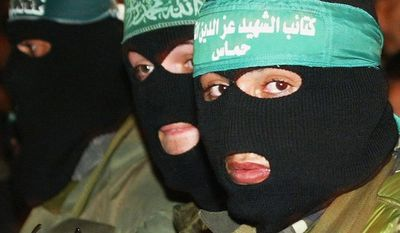 """GAZA CITY, GAZA STRIP -In this file photo, masked Hamas militants march during a demonstration supporting Hamas' Spiritual Leader Sheikh Ahmed Yassin on January 16, 2004, in Gaza City, Gaza Strip. Thousands of Palestinians demonstrated in Gaza Strip towns and refugee camps after the Israeli deputy defense minister stated that """"Yassin is marked for death"""" following a suicide bombing that killed three Israeli soldiers and a security officer in Gaza. (Photo by Abid Katib/Getty Images)"""