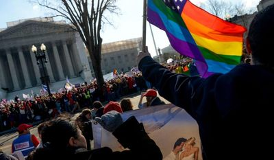 **FILE** Franco Ciammachilli (right) of Washington waves a rainbow flag, a symbol of gay pride, behind supporters of traditional marriage outside the U.S. Supreme Court in Washington as the justices began hearing two days of arguments in cases involving gay marriage on March 26, 2013. (Andrew Harnik/The Washington Times)